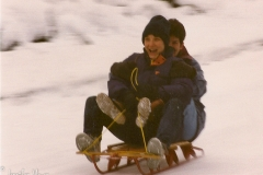 Kathy and me, sledding down our street.