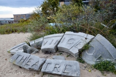 Broken theatre sign on the beach.