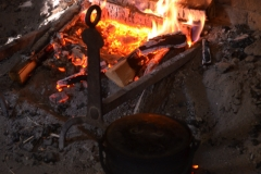 Applesauce is cooked in a bed of coals on the hearth.